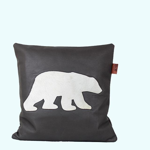 Coussin en cuir nappa gris anthracite découpé avec une forme d'ours polaire sous laquelle est cousue une peau blanche