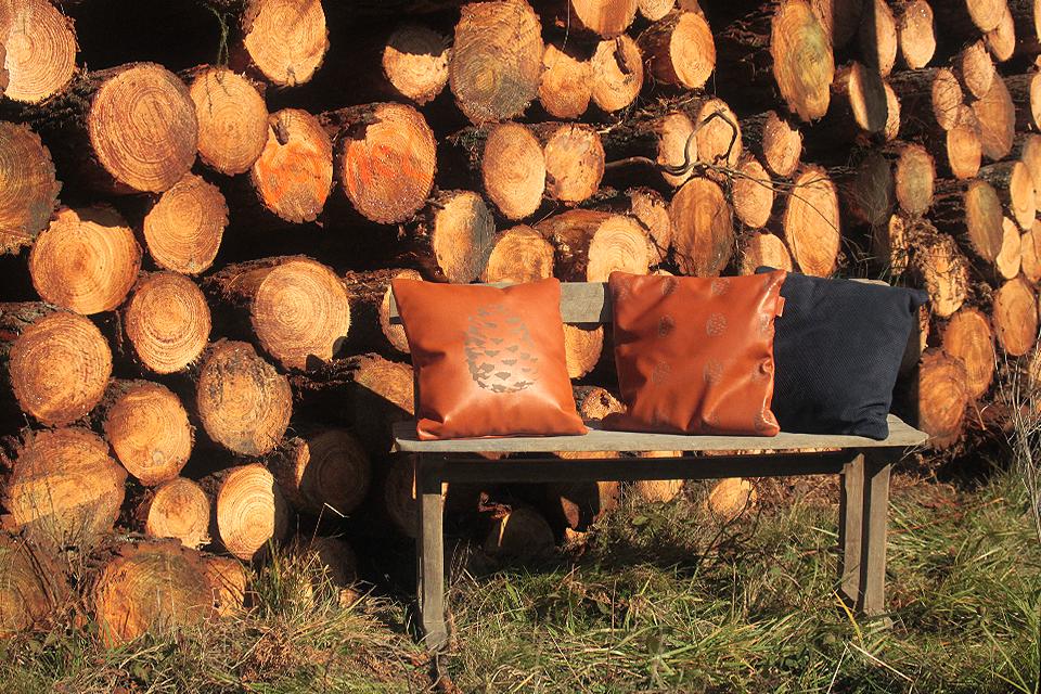 Coussins en cuir sur un banc en bois devant des troncs de pins
