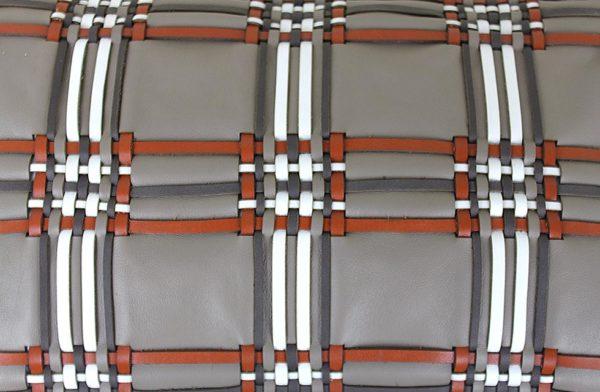 Détail du coussin en cuir tissage écossais, de couleur taupe